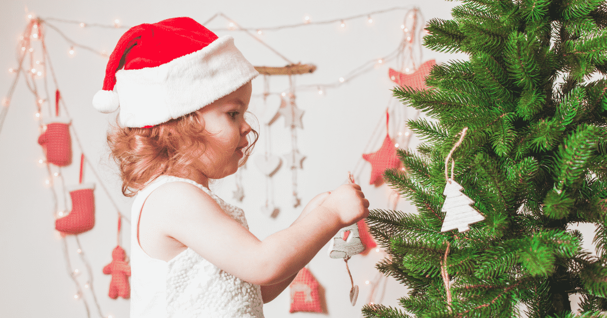 toddler decorating a tree
